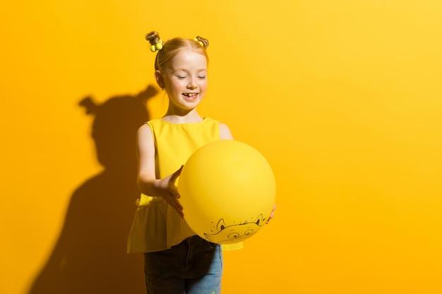 Chica con el pelo rojo sobre un fondo amarillo. la niña está sosteniendo en sus manos y mirando el globo amarillo.
