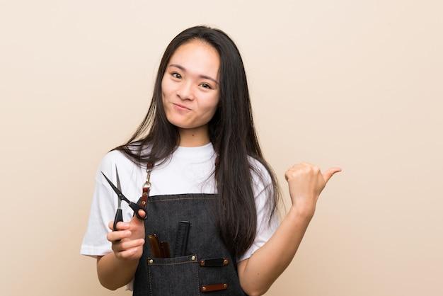 Chica peluquera adolescente apuntando a un lado para presentar un producto