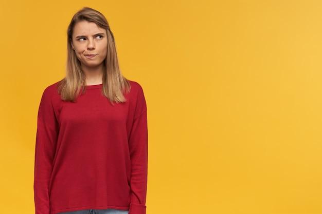 Chica pensativa con cabello rubio. llevaba un suéter rojo. los labios se fruncieron como si dudara de alguna idea. espacio de copia gratuito para su texto