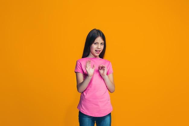 Chica pensativa dudosa rechazando algo contra la pared naranja