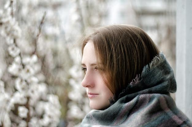 Chica pensativa, envuelta en una tela escocesa mirando a lo lejos, árboles en flor
