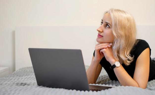Chica pensativa con laptop. selección de bienes en el sitio. compra sueños. esperando una respuesta.