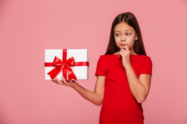 Chica pensativa mirando el regalo en mano y pensando en ello aislado