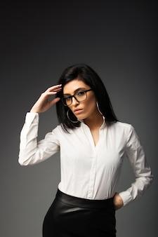 Chica pensativa morena con gafas, en una blusa blanca con una falda de cuero negro.