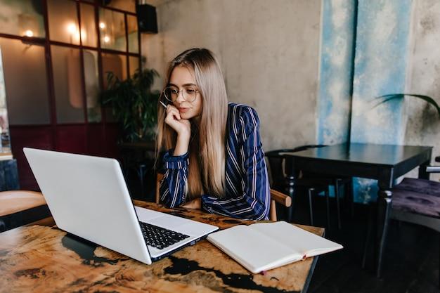 Chica pensativa de pelo largo con gafas mirando la pantalla del portátil. encantadora mujer morena sentada en la cafetería con la computadora.