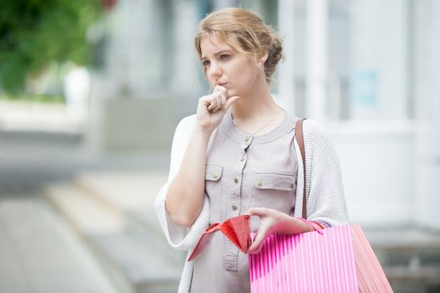 Chica pensativa sujetando su monedero