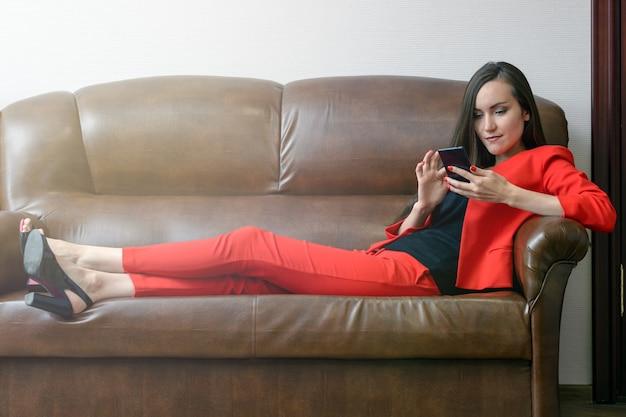 Chica perezosa sentada en el sofá de cuero en la oficina con las piernas dobladas y mira hacia el teléfono inteligente.