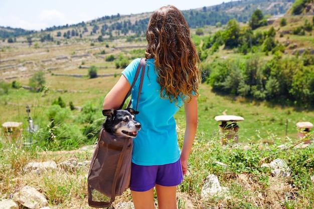 Chica con perro en una bolsa vista trasera mirando montañas