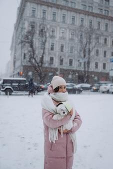 Chica con un perro en sus brazos en una calle de la ciudad, la nieve está cayendo