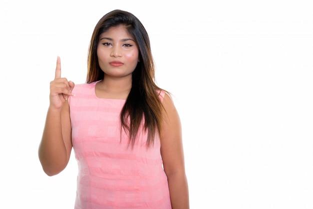 Chica persa apuntando con el dedo hacia arriba