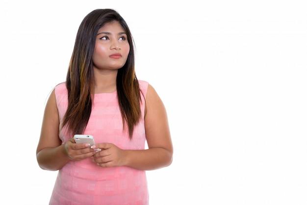 Chica persa pensando mientras sostiene un teléfono móvil