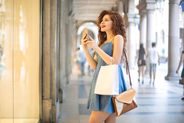Chica de pie frente a un escaparate, haciendo una foto con su teléfono inteligente