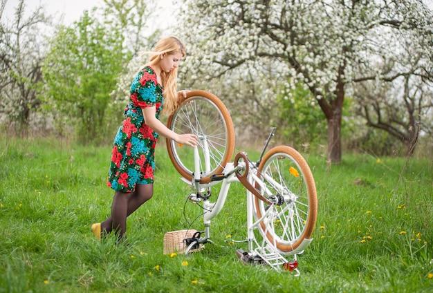 Chica de pie junto a la bicicleta retro blanca boca abajo, explorando la rueda en el jardín de primavera