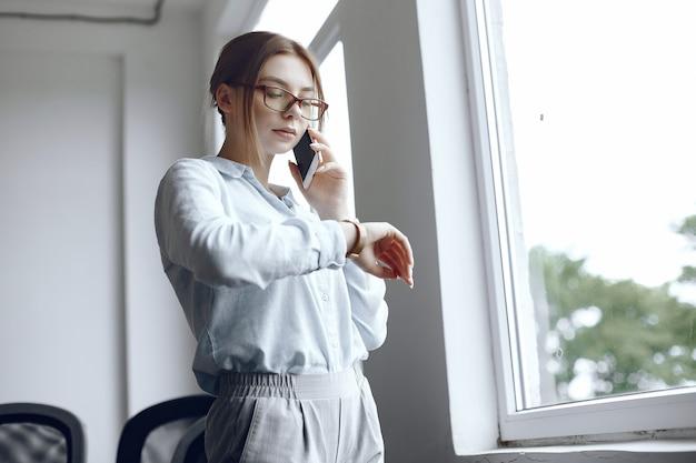 Chica está de pie junto a la ventana. mujer hablando por teléfono. morena mira su reloj