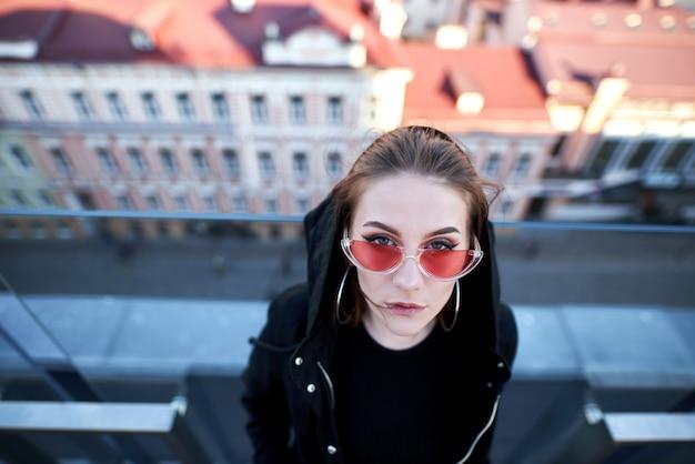 Chica de pie en la valla de vidrio y vidrio se ve la ciudad, con gafas de sol de color rosa.