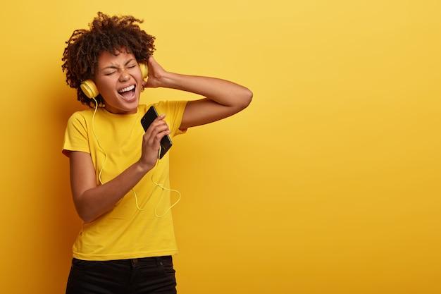 La chica de piel oscura con estilo y complacida disfruta de la música de la lista de reproducción de motivación, disfruta del tiempo libre para escuchar pistas populares