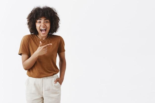 Chica de piel oscura con peinado afro en elegante camiseta marrón divirtiéndose pasando tiempo riendo alegremente y señalando algo divertido a la derecha tomados de la mano en el bolsillo