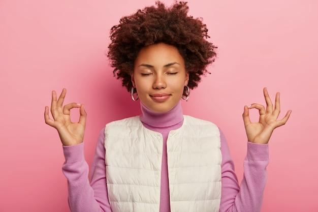 Chica de piel oscura relajada siendo paciente y aliviada, muestra un gesto de mudra zen, practica yoga después del trabajo, vestida con chaleco blanco, se para con los ojos cerrados sobre fondo rosa.