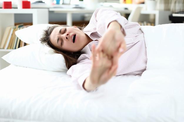 Chica en pijama se acuesta en la cama y se estira, bostezando