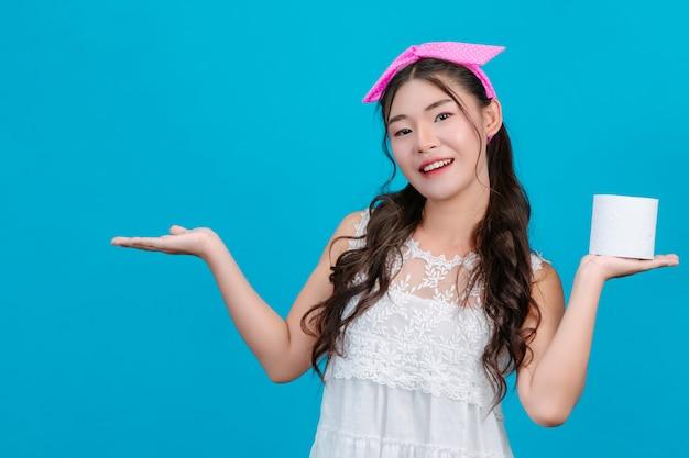 Chica con pijama blanco sosteniendo un papel de seda en la mano en el azul.