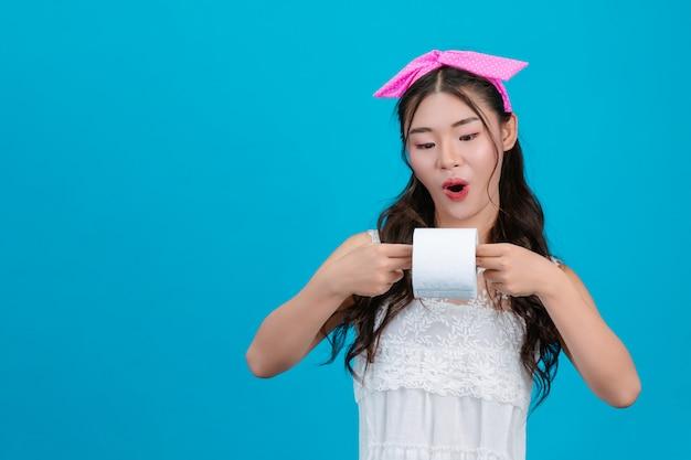 Chica con pijama blanco sosteniendo un rollo de papel de seda en la mano en el azul.