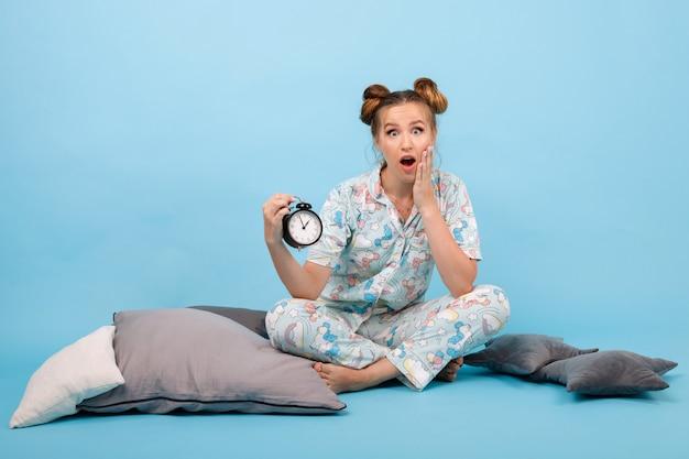 Chica en pijama llega tarde al trabajo. en manos del despertador. niña en un espacio azul
