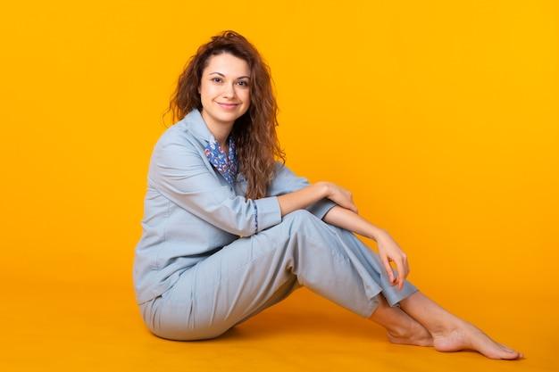 Chica en pijama posando mientras descansa en casa sobre fondo amarillo