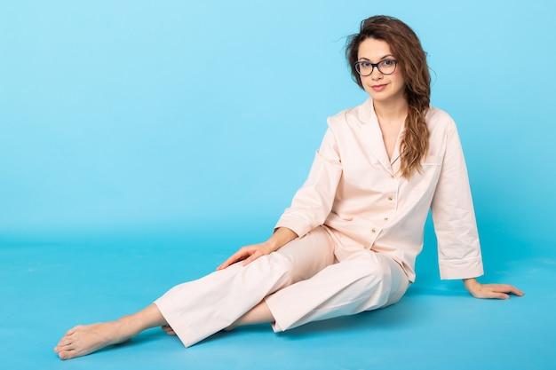 Chica en pijama posando mientras descansa en casa sobre fondo azul.