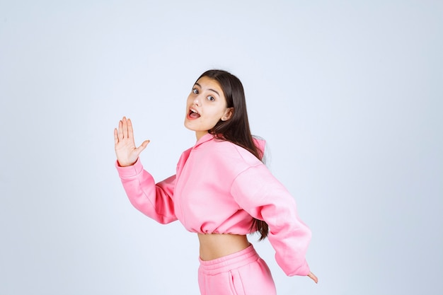 Chica en pijama rosa corriendo desde el lugar.