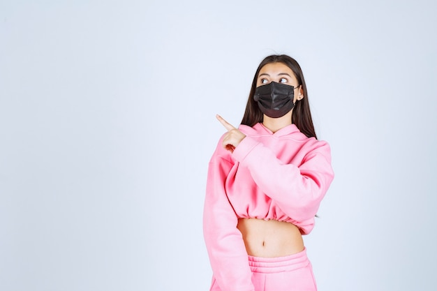 Chica en pijama rosa y máscara negra apuntando hacia el lado izquierdo.