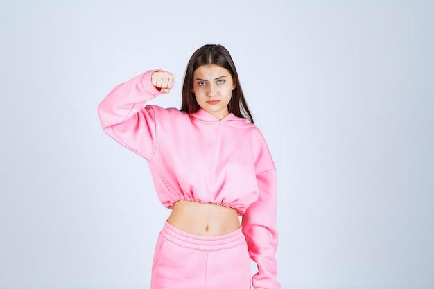 Chica en pijama rosa parece una luchadora y agresiva.