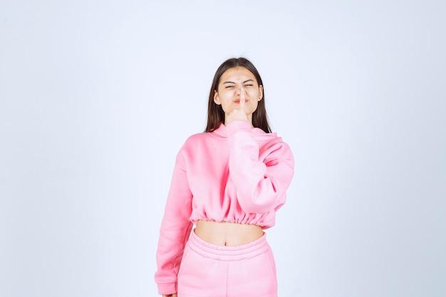 Chica en pijama rosa pidiendo silencio