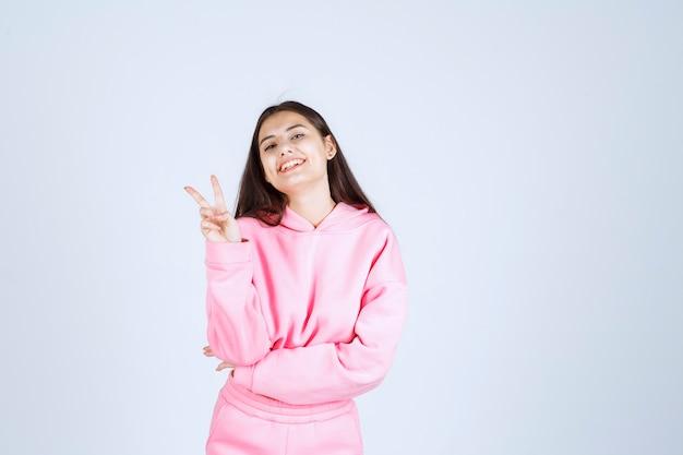 Chica en pijama rosa se siente feliz y muestra un signo de mano positivo.