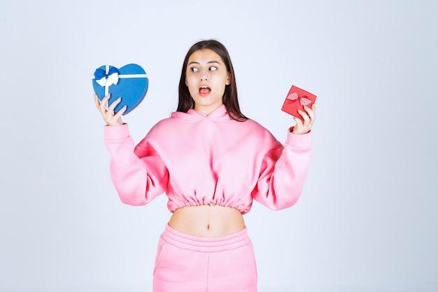 Chica en pijama rosa sosteniendo cajas de regalo con forma de corazón rojo y azul y haciendo una elección entre ellos.