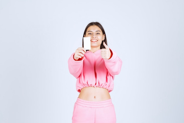 Chica en pijama rosa sosteniendo una tarjeta de visita y mostrando signo de mano de disfrute.
