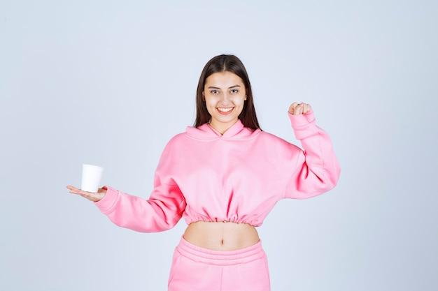Chica en pijama rosa sosteniendo una taza de café y mostrando su puño