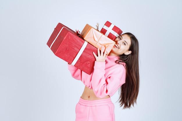 Chica en pijama rosa sosteniendo varias cajas de regalo rojas y sintiéndose feliz.