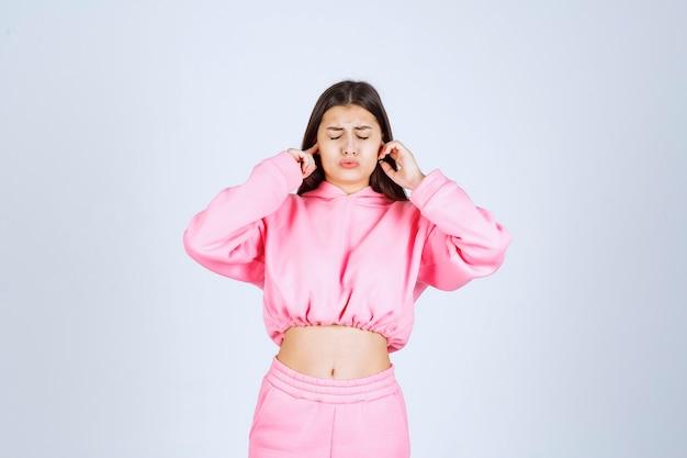 Chica en pijama rosa se ve confundida y pensativa