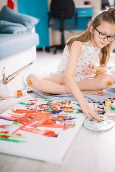 Chica pintando con los dedos sobre lienzo en piso