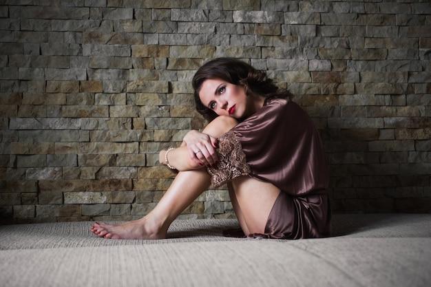 Chica pinup con cabello castaño y maquillaje retro con labios rojos en una bata de baño en un oscuro. niña sentada en la cama. imagen vintage