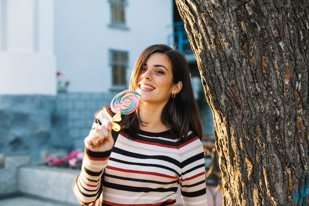 Chica con piruleta colorida junto a árbol