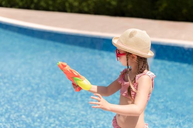 Chica en la piscina jugando con pistola de agua