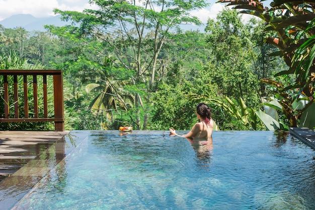 Chica en una piscina privada en bali admira una hermosa vista de las palmeras.
