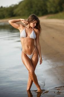 Chica en la playa en bikini blanco