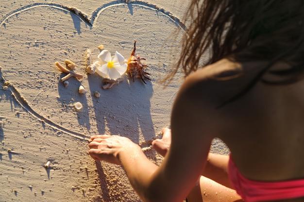 Chica en la playa dibujando un corazón en la arena