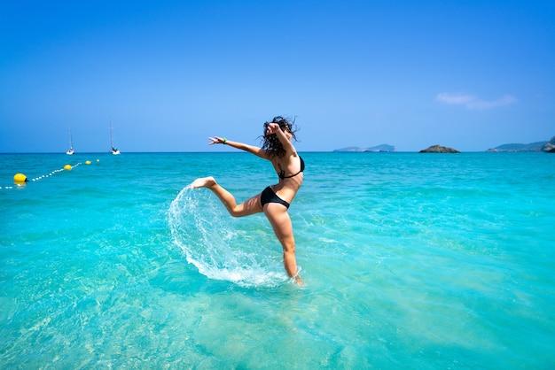 Chica de playa de ibiza salpicando agua en baleares