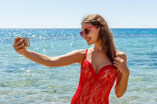 Chica en la playa con un teléfono celular haciendo selfie en día soleado