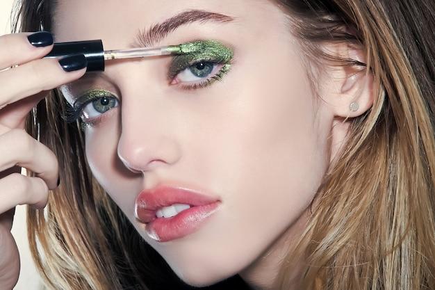 Chica pone sombra de ojos en los ojos con pincel, nueva tecnología. salón de belleza y look de moda, cosmética. cuidado de la piel y rostro. maquillaje, peluquería y cosmética.