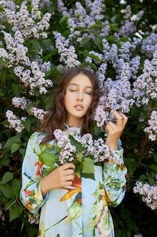 Chica posa en un arbusto de lilas en la primavera. retrato romántico de un niño en flores a la luz del sol