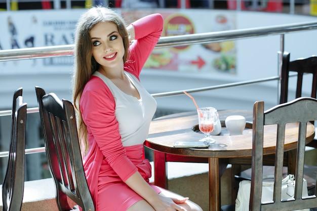 Chica posando con un brazo detrás de la cabeza y sonriendo
